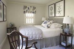 The tailored rectangular headboard in the guest room is upholstered in a pewter gray ultra-suede with contrast indigo piping. These colors are picked up in the pillows and windows with the slightly abstract botanical floral fabric from Dogwood textiles. The large-scale graphic sea life prints help keep the space open and complete the look of the room.