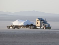 SNCs Dream Chaser test flight craft is hauled across the bed of Rogers Dry Lake at Edwards Air Force Base, Calif., to NASAs Dryden Flight Research Center on May 15, 2013.