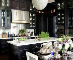 Kitchen with stainless steel and brass hood, marble counters, black cabinets.