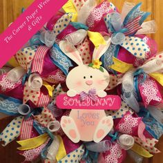 "Easter extra large 28"" round pink, blue, yellow deco mesh wreath with wooden bunny center with wording ""some bunny loves you""."