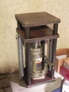 Homemade hydraulic press constructed from steel plate, steel rod, springs, and a bottle jack.
