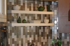 Floating shelves are the perfect solution to an angled wall and allowed us to create a backsplash using Dal Tile's Rittenhouse subway tile using three colors in a matte and glossy finish.