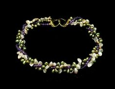 This necklace is made with freshwater pearls, sterling silver beads and clasp. This necklace has different shades of cornflaked Keishi pearls, dark green pearls drops and faceted amethyst. When farming cultured freshwater pearls the oyster is taken care of in a manner to assure that it lives a normal healthy life span. Furthermore, waterways are kept clean and pollutant free to ensure the largest, most iridescent, and blemish free pearls. All jewellery pieces are handmade in North America by…