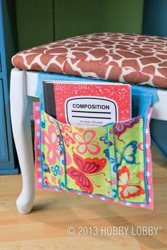 This chair-mounted notebook caddy is a fun, no-sew project. To make it, we cut out a series of felt squares, finishing the edges with pinking shears. Then we glued the squares together.