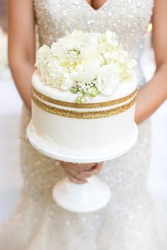 Sparkly Winter Wedding Inspiration from Allure Bridals... glittery gold wedding cake with flower topper