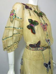 Early 1900s stage gown done in ecru netting with   silk and velvet butterflies top to bottom, front   and back adorned with sequins and   beads....giving the illusion of butterflies in a net.