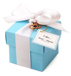 """I Do Wedding Favor Box box size: 2"""" x 2"""" x 2"""" The words that unite you and your spouse will be remembered in a unique and inspiring way with our I Do Wedding Favor Box. This elegant favor box comes in a beautiful teal blue and features a luxurious white satin ribbon. Each box is adorned with interlocking engagement ring and wedding band in gold or silver. Open the box to reveal a delightful treat. Choose from chocolate covered coffee beans, Jordan almonds, or several other scrumptious…"""