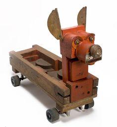 Perro rojo hecho con diferentes moldes de madera y ruedas de un antiguo patín. Miquel Aparici
