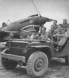 AVG Pilots Pose In Front Of P-40 - For the album five more Flying Tigers pose in jeep car on the flying field. Front seat, from left: Newkirk, Geselbracht, Howard; in back: Bartling and Layher. Newkirk, the man making a face, has shot down 25 Japs so far, had seven or eight when the picture was taken at the end of January. Newkirk and Howard are squadron leaders. Other three are late arrivals.