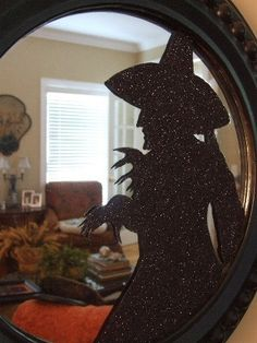 Glittered WICKED WITCH Silhouette Mirror... cut out the silhouette on card stock, apply glue and then glitter.  Spray paint the frame of the mirror black then add the silhouette!