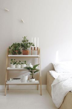Minimalist modern organic bedroom interior design idea: use a ladder shelf to hold candles, potted plants and books, as an alternative to a traditional bedside table. White sheets, white pots and cera