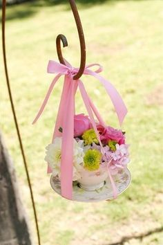 Aisle Decor: Shabby chic tea cup & saucer filled with colorful fresh blooms (probably a good idea to hot glue the cup & saucer together). A pink satin ribbon adds a pretty finishing touch & makes the perfect hanger.