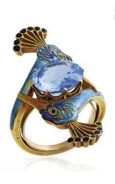 RENÉ LALIQUE - AN ART NOUVEAU SAPPHIRE AND ENAMEL RING, CIRCA 1900. Centring an oval-cut sapphire between two peacock heads applied with blue and black enamel, with French assay mark for gold, signed Lalique. #GoldJewelleryArtNouveau