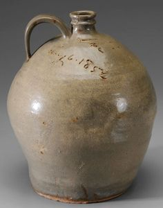 IMAGE: An Edgefield incised stoneware Dave [Slave Potter] jug, creamy olive-brown alkaline glaze, Dave Drake, South Carolina, circa 1852