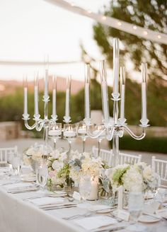Tables were swathed in soft toned fabric and brought to life by tall centerpieces of white orchids and roses surrounded by floating candles in staggering heights. Wedding Decorations, Wedding Venues, Wedding Flowers, White Wedding. Photo by Sylvie Gil Photography