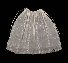 White muslin embroidered with white linen threads. Flowering vines and sprigs of flowers. Long and short, stem, chain stitch, drawn work. Apron gathered to a silk gros grain ribbon tie at waist. A few brown spots and holes in left corner of apron.
