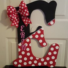 Minnie Mouse Theme Wooden Letter These Minnie Mouse themed letters are great for your little girl who loves the beloved Disney character. It consists of glitter, Minnie mouse's hairbow, and her dress design. The letter is 2 feet tall from longest points, Wooden Letter Crafts, Painting Wooden Letters, Diy Letters, Painted Letters, Letters For Wall, Decorative Wooden Letters, Wood Letters Decorated, Letter Door Hangers, Letter Wall