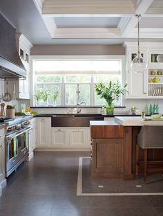 Stunning kitchen with glass pendants hung from a coffered ceiling over a dark stained island with light stone counter lined with gray leather counter stools paired with drop-down butcher block topped prep island attached to the end.