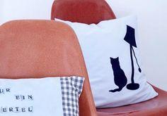 """Kissen für Katzenliebhaber    Das schlichte Kissen mit """"Hotelverschluss"""" ist aus Babycord genäht. Das Kätzchen in Wartestellung ist mit weicher Flockfolie aufgebügelt.    Das brauchen Sie:  - Babycord, Hellblau, 42 x 92 cm  - Poli-Flock Prime-Folie in Dunkelblau, ca. 50 x 50 cm, Preis: ca. 10 Euro, erhältlich bei www.jlgraphics.de  - Inlet, 40 x 40 cm  - Nähmaschine, Bügeleisen, Schere, Garn, Maßband, Stecknadeln"""