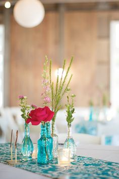 turquoise glass jar /vases...with turquoise runner compliments this centerpiece