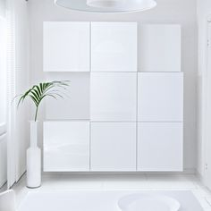 A room with BESTÅ Storage combination in white on the wall, next to FYLLIG Vase in White