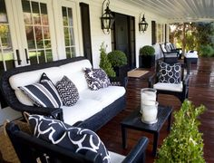 White Front Porch with Black Accents (front door, light fixtures, shutters, furniture) and dark-stained floor - Kriste Michelini Design via Design Chic
