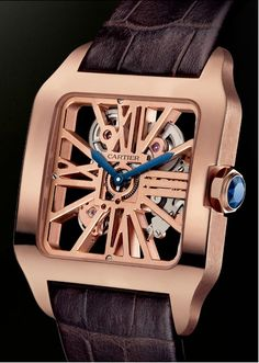 Cartier Santos-Dumont Skeleton Rose Gold. The blue sword-shaped hands and blue faceted sapphire in the winding crown add a touch of bright color, and the brown alligator leather strap completes the package...