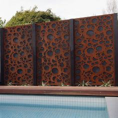 Rusted corten bubbles screen by a pool