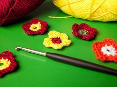 Häkelbumen in bunten Farben für Taschen, Mützen oder Pullover oder als Deko aus Wolle. Häkeln Sie die Blumen mit dieser Gratis-Anleitung einfach selbst.