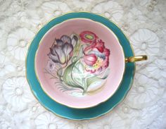Susie Cooper English bone china teacup set elaborate turquoise 1960s tropical flower teacup and saucer pink background inside with colorful bouquet an exceptionally pretty teacup set excellent vintage condition with minor wear on turquoise area gold gilt rims are intact, as is tropicl flower bouquet what a beautiful addition to your collection thanks for stopping by !  shipping is for USA  https://www.etsy.com/shop/SharetheLoveVintage?ref=si_shop