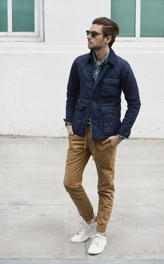 Wear a navy quilted field jacket and camel chinos for a trendy and easy going look. Why not add white low top sneakers to the mix for a more relaxed feel?   Shop this look on Lookastic: https://lookastic.com/men/looks/field-jacket-denim-shirt-crew-neck-t-shirt/10994   — Navy Quilted Field Jacket  — Black Sunglasses  — Khaki Chinos  — White Low Top Sneakers  — Blue Denim Shirt  — White and Black Horizontal Striped Crew-neck T-shirt