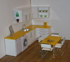 1:12 kitchen in gloss white with yellow worktops    Solid acrylic worktops on high gloss units make for a bright contemporary feel.