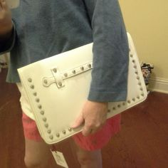 """Studded Envelope Style Clutch NWT. Barely off white with silver studs on one side. Silvertone hardware. Accordion bottom with full length zipper. Extra strap, detachable, included. 2 interior, open pockets. Dimensions: 14.5"""" wide x 9.25"""" tall x 2.5"""" wide at bottom. Adjustable strap is 50"""" including hardware. Faux leather. Faint light pink spot of discoloration on back side about the size of a dime, but generally not noticeable. Yellow also available in a separate listing. :) Mad About Style…"""