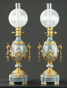 A pair of ormolu-mounted bleu turquin marble oil lamps THIRD QUARTER 19TH CENTURY, THE GLASS SHADES LATER