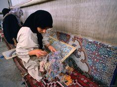 Women weaving carpets in Esfahan, Iran.