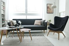 salon w stylu skandynawskim z czarną sofą i ciemnym fotelem