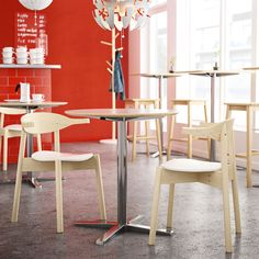 Café with high and low round tables, bar stools and chairs in solid wood.