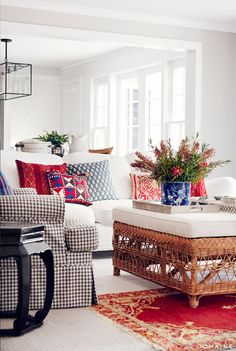 White sofa with patterned pillows and checkered armchair