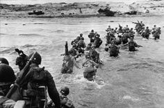 US troops disembark from landing crafts during D-Day 06 June 1944 after Allied forces stormed the Normandy beaches. D-Day, 06 June 1944 is still one of the world's most gut-wrenching and consequential battles, as the Allied landing in Normandy led to the liberation of France which marked the turning point in the Western theater of World War II. (AFP / Getty Images)