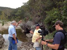 Mark Stitzer filming Jon Cradit explaining a water feature to rancher Todd Figg in Uvalde, west of San Antonio.