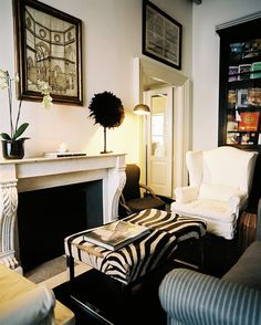 A zebra-print ottoman anchors a traditional living room, where with a pair of white wingback chairs cozy up to a whit fireplace.