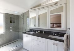 Ring pull hardware, gray glass subway tile, vanity mirrors with storage. Marin Bungalow by Feldman Architecture