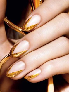 "Channeling Gatsby glamour with golden nails. Try it: 1) Apply a coat of pearly ivory polish and let dry. 2) Starting at cuticles, paint a gold strip along outer edges to form a triangular shape at the tips. (Try Colour Riche Nail in Because You're Worth It). 3) Paint outer edges with a sparkly gold like The Statement Piece. Need help staying in the lines? Use a white nail pen to trace a ""V"" over the base coat."