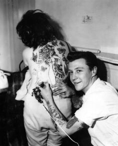 Unknown black & white photograph of tattoo artist in action. Bet these grandparents are totally Bad Ass now!!