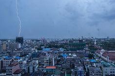 Lightning strikes during a thunderstorm over the city skyline