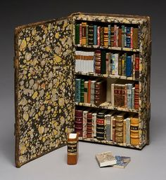 Todd Pattison of Andover, Massachusettes, altered a found 19th C leather binding with fore-edge clasps to create a little library containing 72 little books.