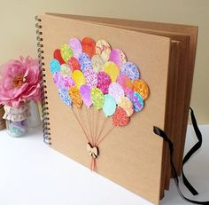Beautifully hand-decorated scrapbook album - makes a perfect baby album / scrapbooking, photo album and even wedding comments book. The cover is so colourful, displaying 28 beautiful bright balloons, real cotton thread and a gorgeous wooden bow.  This lovely book has a high quality hardboard front and back, with 40 sheets of heavyweight 200gsm kraft card, providing 80 pages! Perfect for your scrapbooking, or just add some photo-corners to use as a fabulous photo album!  Your album can also…