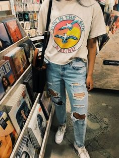 baggy white vintage t-shirt, with a colorful graphic print, worn with ripped, pale blue jeans, and white sneakers, by a girl standing in a record store