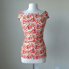 Sunset orange floral off the shoulder top tee 95% rayon, 5% spandex, three silvertone buttons on each shoulder, ruching detail around waistline, Measurements in inches - Size XS: bust 32.5, length 23.  Size S: bust 34, length 33.  Size M: bust 36, length 23.  Size XL: bust 42, length 25. White house black market made for outlet top White House Black Market Tops