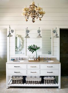 The sleek vanity in the master bath is punched up by a beachy seashell chandelier and chrome sconces by Rejuvenation. | Lonny.com